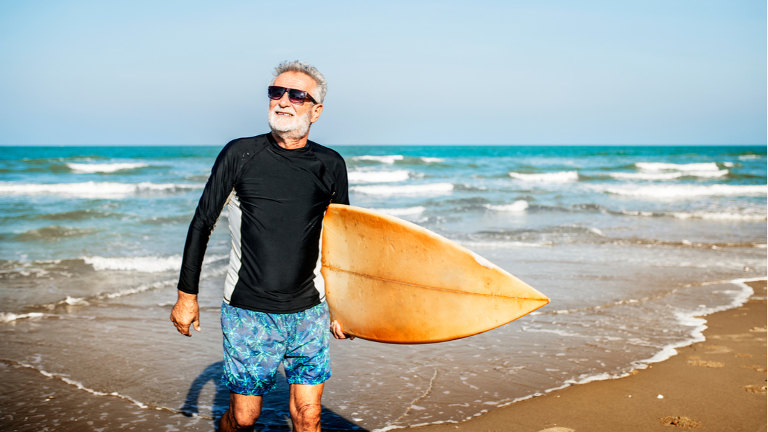 A senior strolls on the beach after surfing.