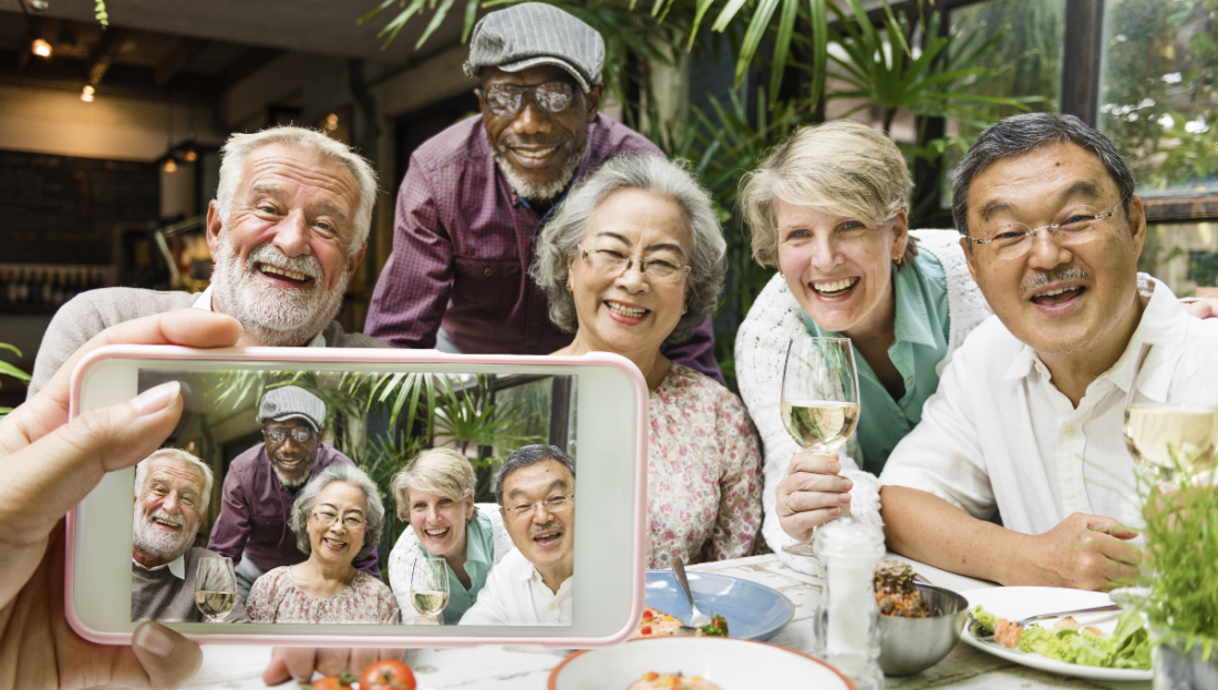 A group of seniors pose for a cell phone photo during Medicare Open Enrollment.