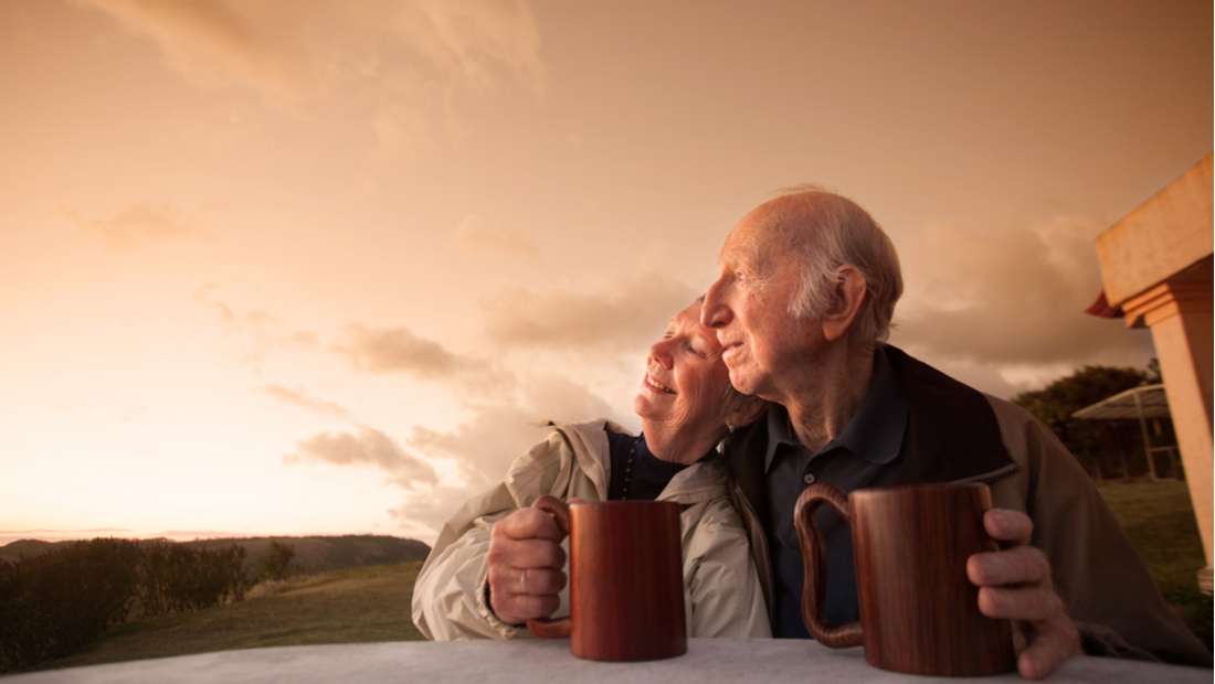 Two seniors sip coffee as the sun sets.