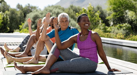 A group of seniors do yoga together outdoors.