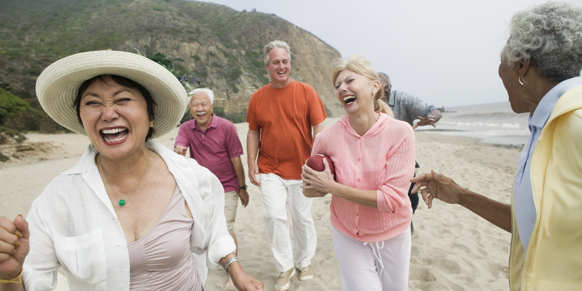A group of seniors laughing on the beach.