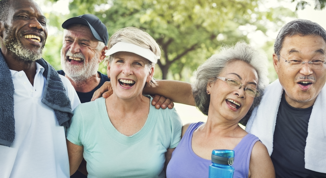 A group of seniors smile for the camera after exercising in the park.