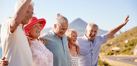 A group of seniors smile and wave by the side of a road.