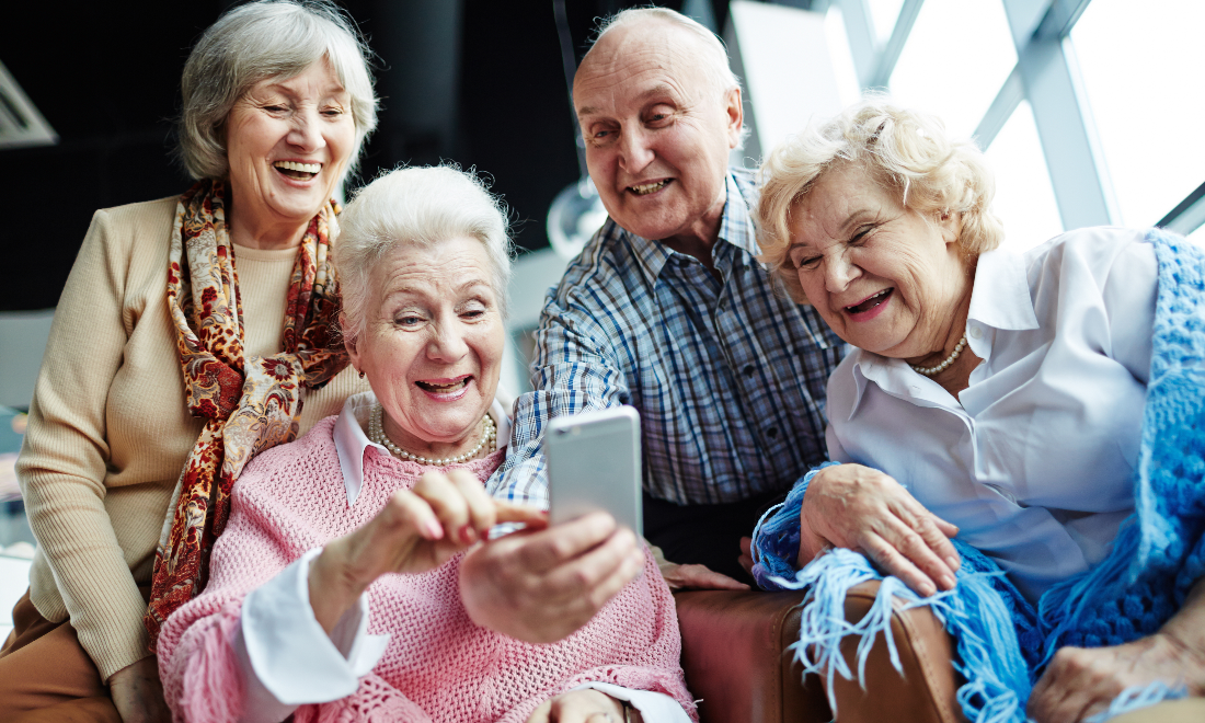 A senior woman holds up her cell phone for several friends to see