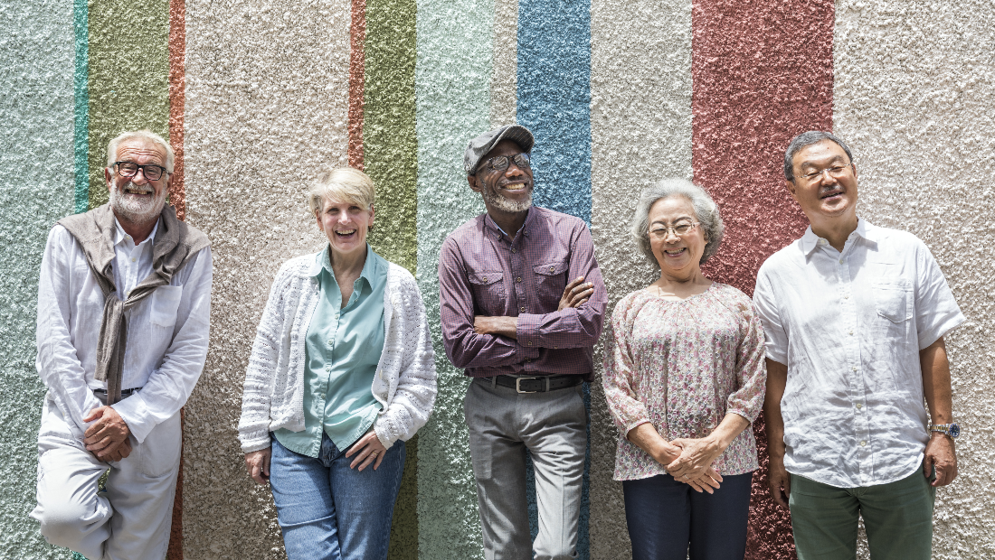 A group of seniors poses for a photo in front of a striped wall.